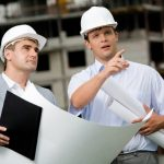 Photo of young engineer showing something to his colleague during meeting at building site